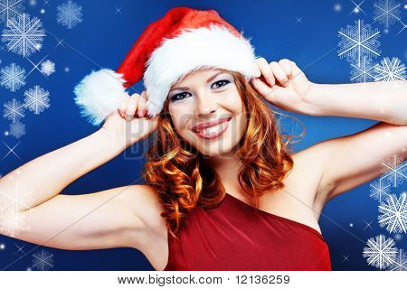 Cute happy Santa helper girl posing on blue studio background with snowflakes