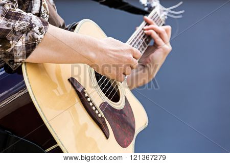 woman's hands playing acoustic guitar closeup