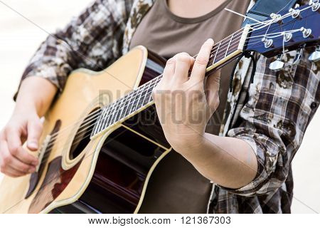 woman playing on classic acoustic guitar