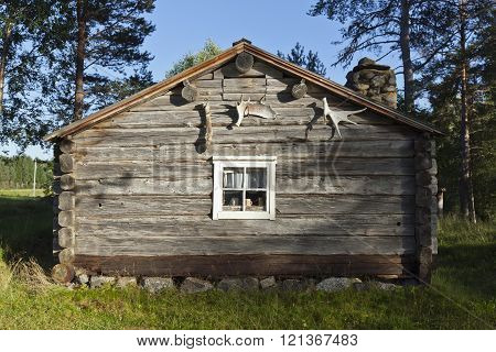 BACKE, SWEDEN ON AUGUST 15. View of a wooden homestead, Folk Museum on August 15, 2013 in Backe, Sweden. Moose horn on the wall, timber wall in late evening lit. Editorial use.