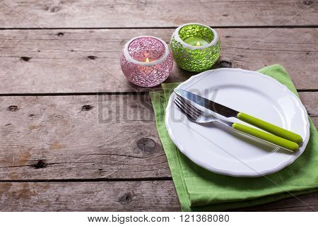 Romantic  Table Setting. Decorative Lanterns, Knife And Fork On White Plate On Vintage Wooden Backgr