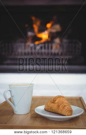 View of coffee and croissant on a table in the living room