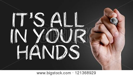 Hand writing the text: It's All In Your Hands