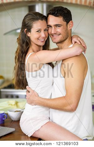 Portrait of romantic young couple cuddling on kitchen worktop