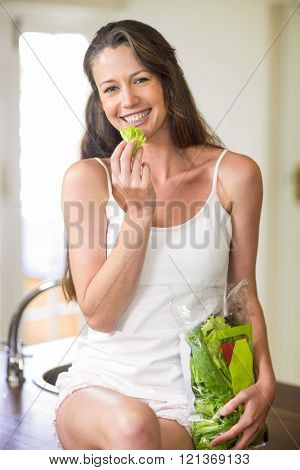 Portrait of happy young woman sitting and holding vegetables on kitchen worktop