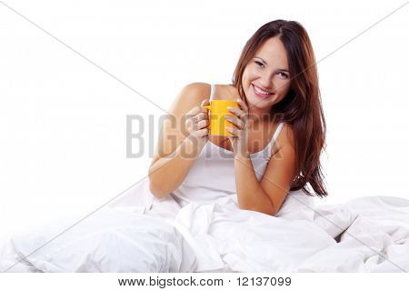 Studio portrait of young beautiful woman on bed holding cup of tea