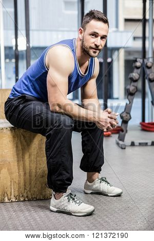 Muscular man sitting on wooden block at the crossfit gym