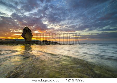 Rock green moss with sunrise background at Pantai Batu Payung ( Umbrella Rock Beach) lombok Indonesia.