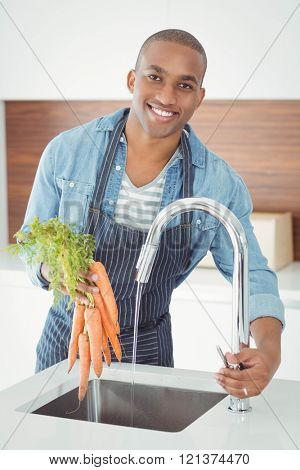 handsome man washing carrots in the kitchen