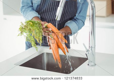 Mid section of man washing carrots in the kitchen