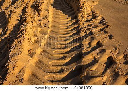 Embossed Trail Excavator Tracks On The Wet Sand.