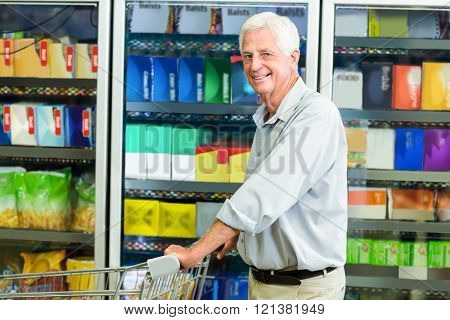 Smiling senior man pushing cart at the supermarket