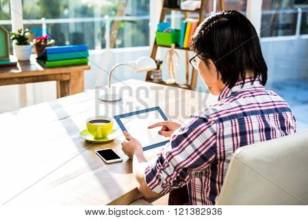 Over shoulder view of casual man using tablet in office
