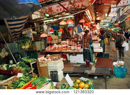 Customers Of Outdoor Market Choose Seafood, Fruits And Vegetables On Busy Narrow Street