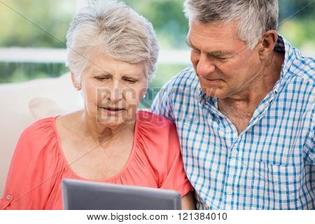 Doubtful senior couple using tablet on the sofa