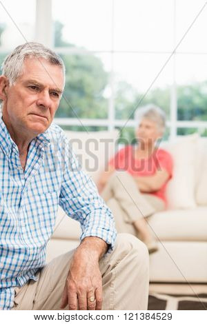 Upset senior man after arguing with wife in the living room
