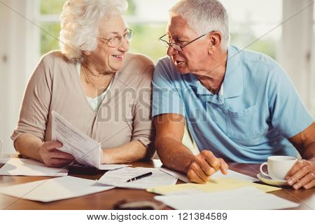 Senior couple counting bills at home