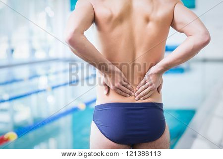 Fit man with back ache at the pool