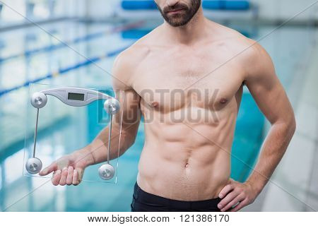 Fit man holding a weighting scale at the pool