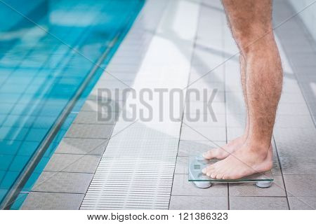 Fit man on weighting scale at the pool