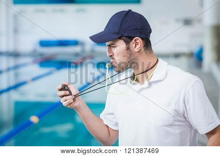 Handsome trainer blowing whistle and looking at stopwatch at the pool