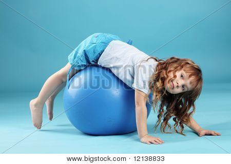 Child with gymnastic ball on bleu studio background