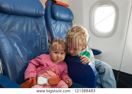 kids travel by plane - little boy and toddler girl in flight
