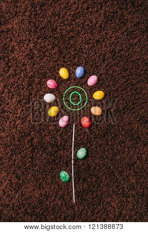 Abstract Flower With Colored Eggs On The Carpet.easter. Flat Lay.