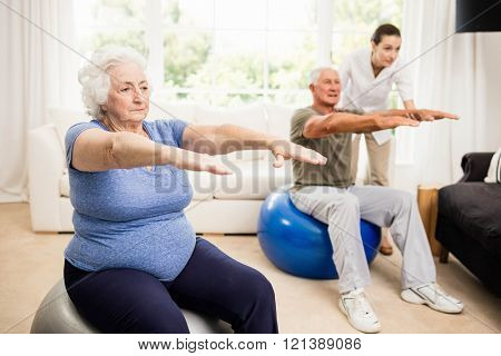 Physiotherapist helping patients with exercises at home