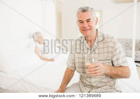Peaceful senior man holding glass of water at home