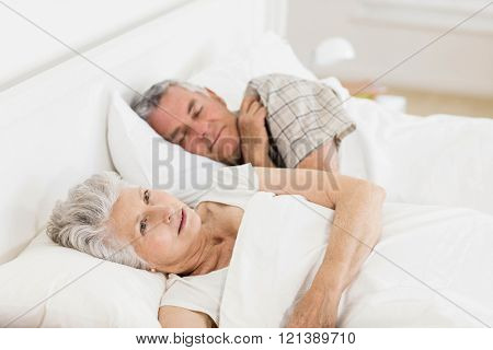 Mature woman awake in bed while her husband is sleeping
