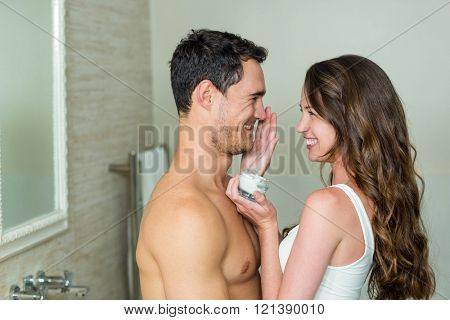 Woman smiling while applying moisturizer on manâ??s face