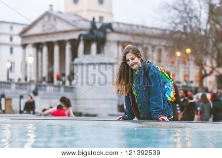 Young Woman Looking At Herself Into A Fountain In London
