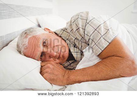 Sick senior man lying on bed in bedroom