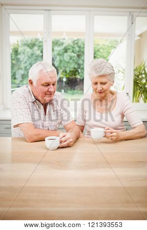 Senior couple talking to each other while having coffee in kitchen