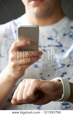 Young Man Synchronizing Smart Watch With Mobile Phone