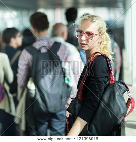 Young blond caucsian woman waiting in line.