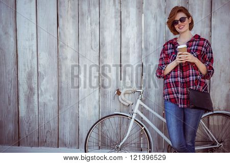 smiling hipster woman with coffee and a bicycle, standing against a wooden background