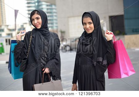 Emarati Arab women coming out of shopping in Dubai United Arab Emirates.