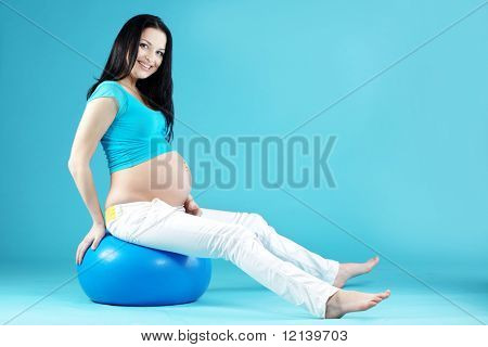 Portrait of pregnant woman on blue