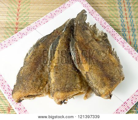 Asian Food and Cuisine A Plate of Oriental Food Deep Fried Gourami Fish or Snakesskin Fish.