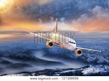 Airplane in the sky over winter Alps at amazing colorful sunset