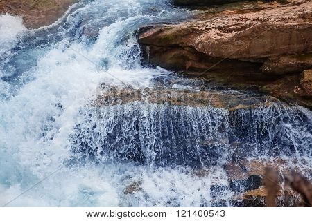 waterfall with blue water and rocks in sunlight