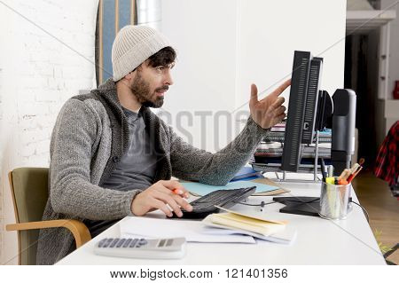 young attractive man in hipster beanie and trendy style businessman working in busy desk holding pen using desktop computer at home office as creative designer in freelance business success