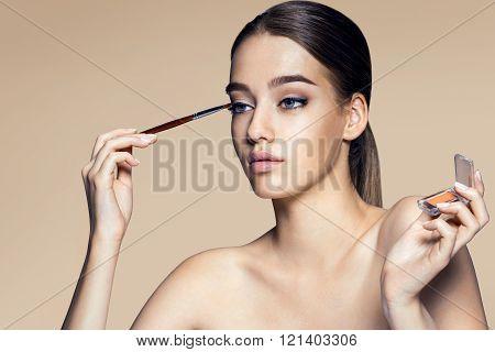 Beautiful young woman touching her perfect skin