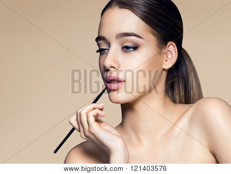 Charming young babe with brush for lipstick