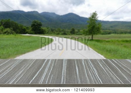 empty wooden table with road and mountain in countryside  blur background