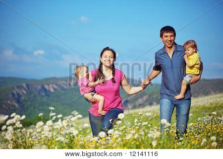 Feliz familia con gemelos de descanso al aire libre