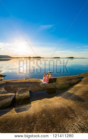 Young woman with laptop by the lakeside