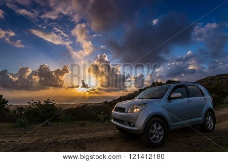 Gray car (crossover utility vehicle) on ground road against beautiful sea sundown.